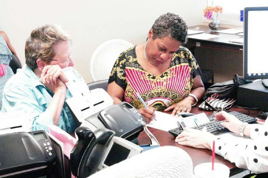Pam Kunkle, right, and Connie Moberley, left, review and sign a marriage application Saturday in Montgomery County. This is the first same-sex couple to purchase a marriage license in the county following the U.S. Supreme Court's ruling Friday.