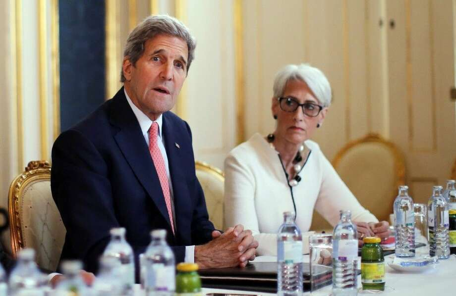 U.S. Secretary of State John Kerry, left, talks to reporters alongside U.S. Under Secretary for Political Affairs Wendy Sherman as they meet with the Iranian delegation at a hotel in Vienna, Austria, Saturday. Photo: Carlos Barria