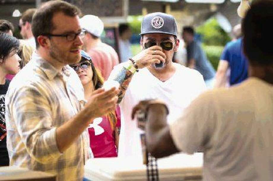 The Woodlands residents Adam Smith, left, and Paul Turner, right, try beer samples from Houston-based 8th Wonder Brewery during The Woodlands Craft Beer and Music Festival on Saturday at Town Green Park. Photo: Michael Minasi