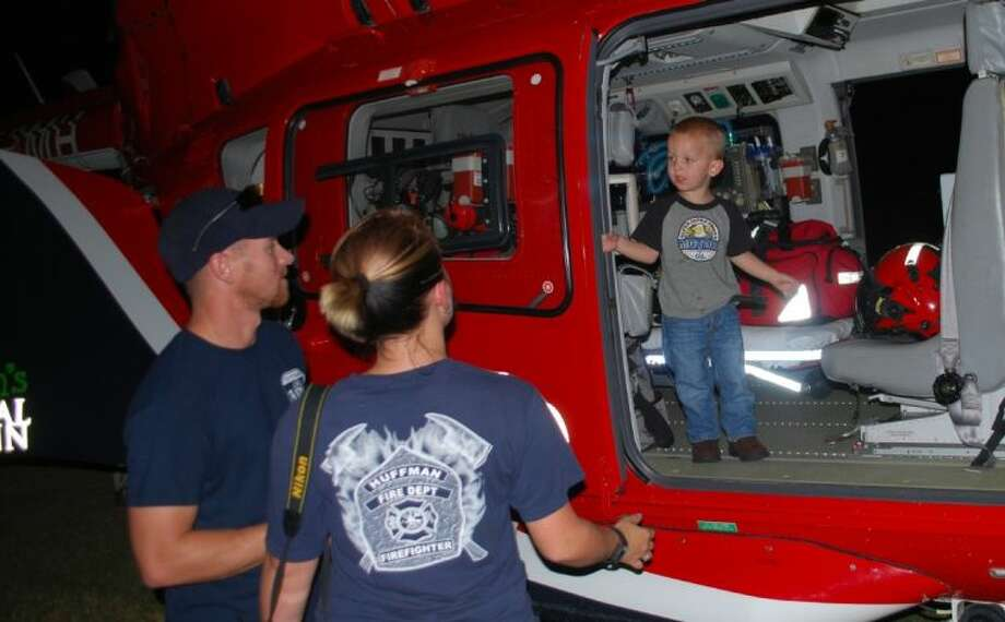 Firefighters and their families examined the Life Flight helicopter that visited Huffman Sept. 17 as part of a joint training event with Huffman and Atascocita fire departments. Shown inside the helicopter is Kayden Jackson and on the outside Wayland Jackson and Amber Jackson. Photo: ANTHONY J. TURNER