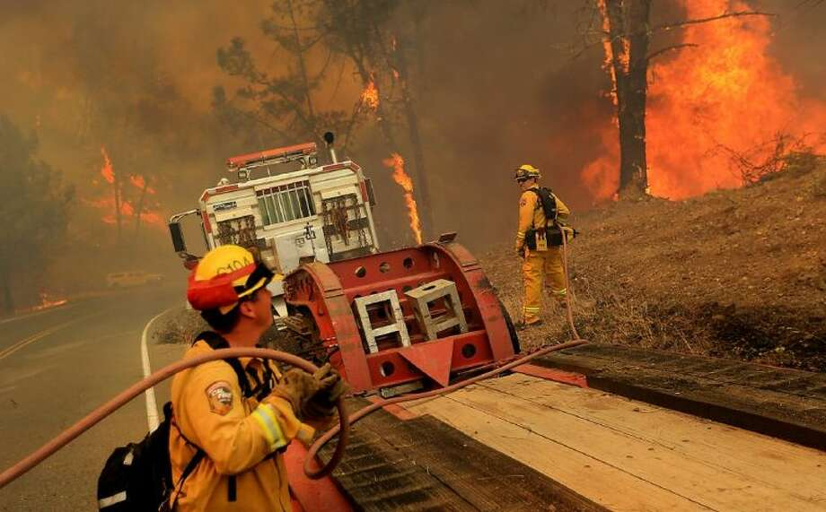 The Cal Fire helitack crew from Boggs Mountain puts out flames around a Cal Fire dozer transport as the Butts Canyon fire jumps Butts Canyon Road, Tuesday, July 1, 2014 outside Middletown, Calif., near the border between Napa and Lake counties. By early evening 140 homes were evacuated and 2,500 acres were burned. Photo: Kent Porter