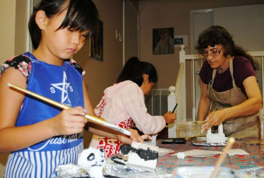 Selina Xia, of The Woodlands, paints on her Panda Box as The Woodlands Art League President Joella Wheeler assists Crystal Pan, of Shangai, China, with her Horse Box Tuesday at The Woodlands Art League. WAL is holding art classes for children, teens and adults this summer.