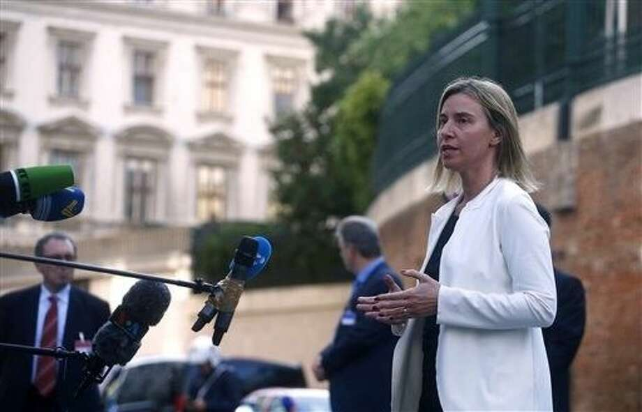 European Union foreign policy chief Federica Mogherini talks to reporters outside the Palais Coburg hotel where the Iran nuclear talks meetings are being held in Vienna, Austria, Sunday. A senior U.S. official acknowledged Sunday that Iran nuclear talks will go past their June 30 target date, as Iran's foreign minister prepared to head home Sunday for consultations before returning to push for a breakthrough. Photo: CARLOS BARRIA