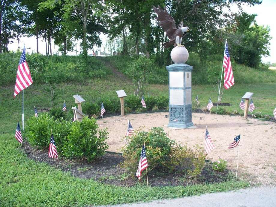 Flags adorn the Honor Flight Eagle Garden in Memory Park. This photo was taken in 2010, shortly after the garden was dedicated. It has matured now, and includes large plants, signs honoring each branch of the military and a bench.