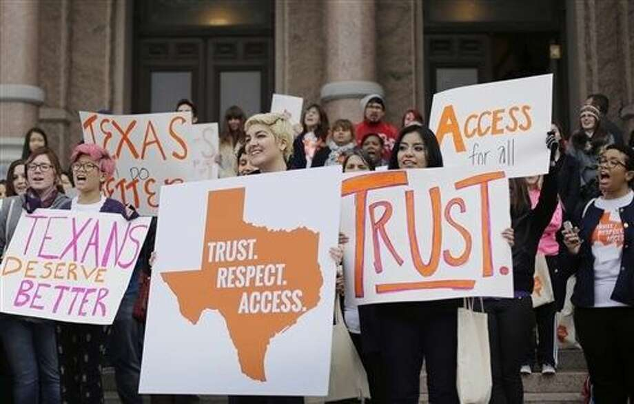 FILE - College students and abortion rights activists hold signs during a rally on the steps of the Texas Capitol in Austin in February. The Supreme Court refused on Monday to allow Texas to enforce restrictions that would force 10 abortion clinics to close. Photo: Eric Gay