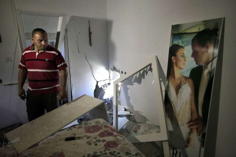 Avihai Giorno stands in his bedroom by a wedding photo of him and is wife Tammy after a rocket fired by Palestinian militants in Gaza landed in the southern town of Sderot Thursday.