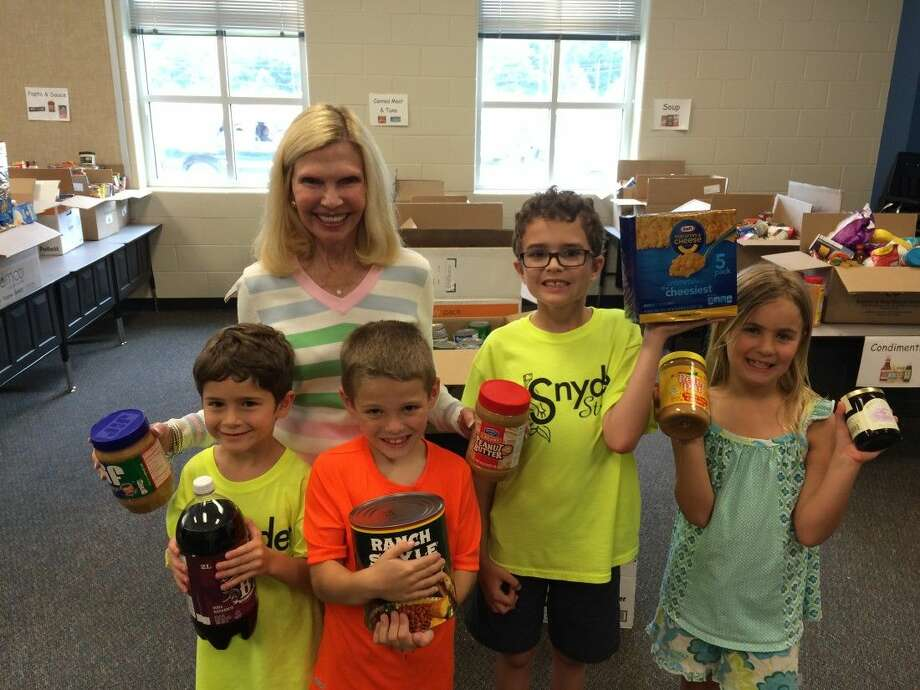 """Students at Ann K. Synder Elementary School collected and donated 2,684 pounds of food for the Interfaith of The Woodlands Food Pantry as part of the second annual """"The Big Event"""" Food Drive. Pictured with Dr. Ann Snyder, President and CEO of Interfaith of The Woodlands are student ambassadors from the first and second grade."""