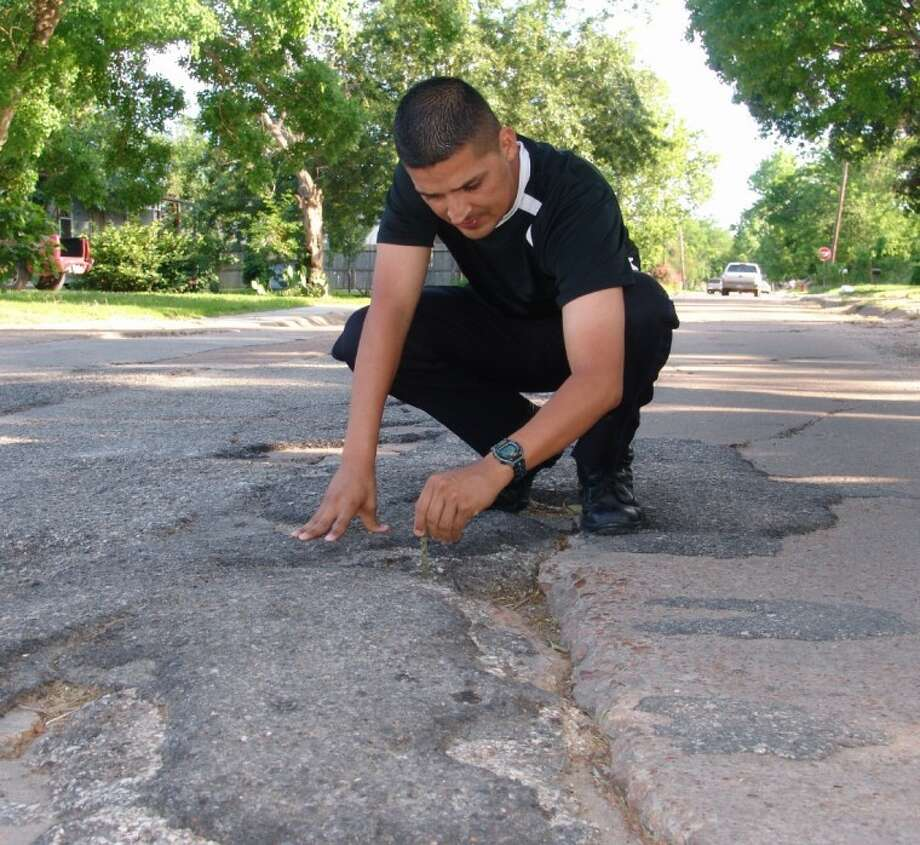 Councilman Orlando Ybarra inspects Witter Street. Ybarra said funds to repair the road were diverted to other projects after he criticized the hiring process that selected a department head's spouse for employment by the city. Photo: JEFF NEWPHER