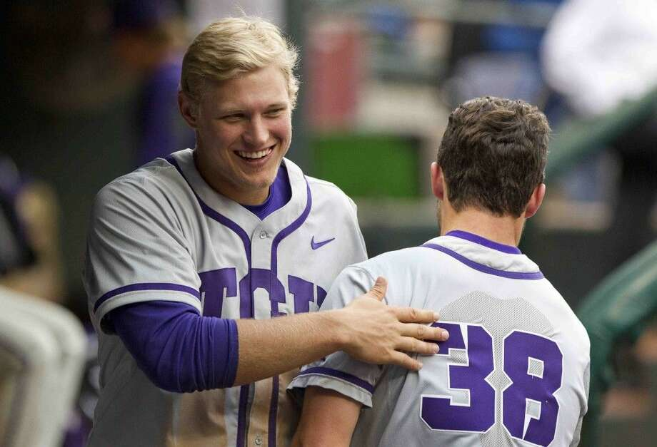 TCU's Luken Baker, a former Oak Ridge player, jokes with Zack Plunkett during the fourth inning of an NCAA baseball game against Houston at the Houston College Classic at Minute Maid Park Sunday. Photo: Jason Fochtman