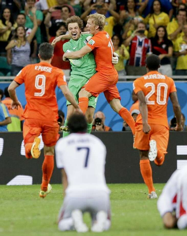 Teammates mob Netherlands goalkeeper Tim Krul after he made the final save in a penalty shootout during a World Cup quarterfinal match against Costa Rica on Saturday at Arena Fonte Nova in Salvador, Brazil.