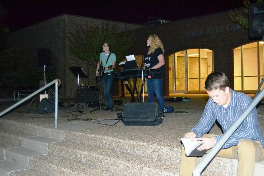 Conroe High student Reed Sowell, right, prepares to speak at See You at the Pole early Wednesday morning in front of the Conroe High Career and Technology building. In the background, his brother Brian and Conroe High senior Rachael Sutton lead praise and worship for the student body.