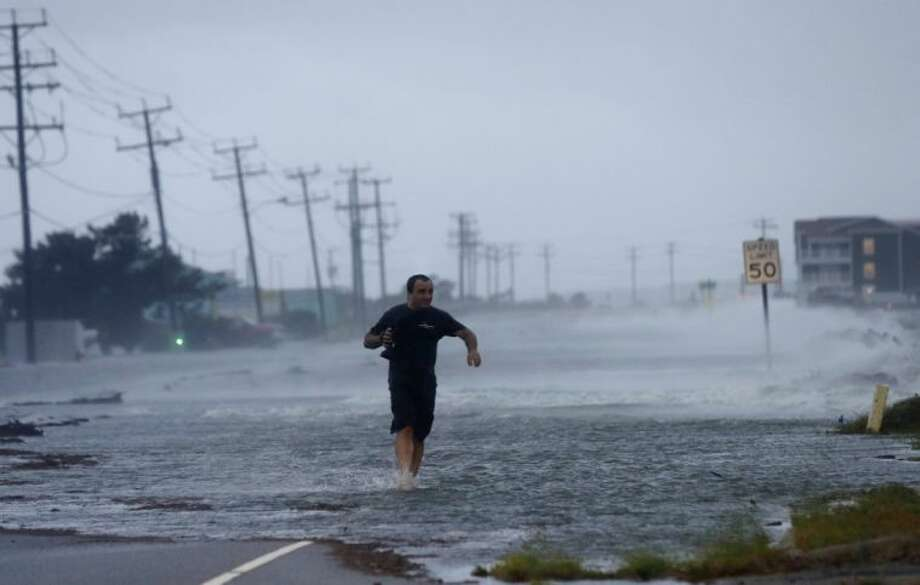 A man crosses a flooded Highway 64 as wind pushes water over the road as Hurricane Arthur passes through Nags Head, N.C., Friday.