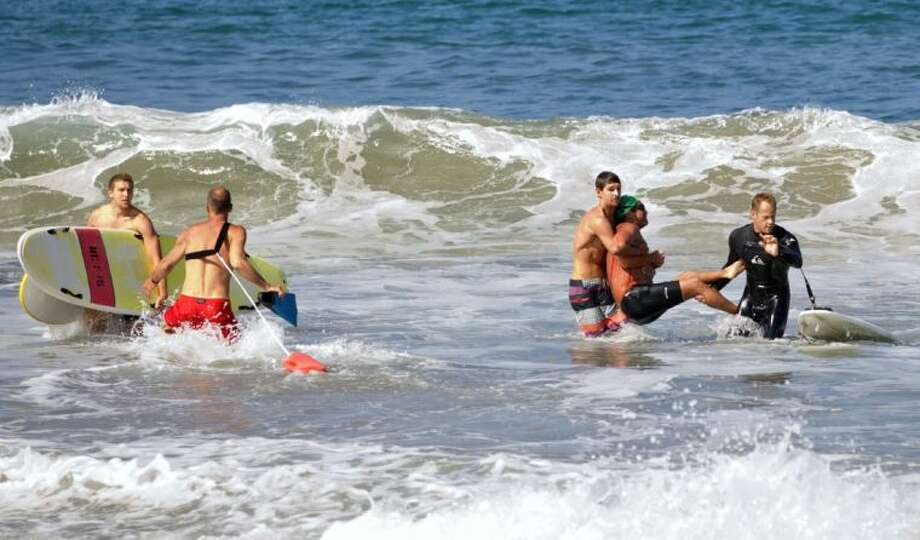 In this photo by Laura Joyce of goofyfootphotography.com, two men carry a swimmer, second from right, after he was bitten by a great white shark, as lifeguards close in at left in the ocean off Southern California's Manhattan Beach, Saturday, July 5, 2014. The man, who was with a group of long-distance swimmers when he swam into a fishing line, was bitten on a side of his rib cage according to Rick Flores, a Los Angeles County Fire Department spokesman. The man's injuries were not life-threatening and he was taken to a hospital conscious and breathing on his own, Flores said. Photo: Laura Joyce