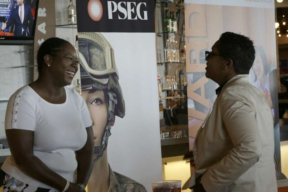 Sophia Lewis, left, with PSEG Long Island, speaks to an attendee about employment opportunities during a job fair at Citi Field in New York. Photo: Mary Altaffer