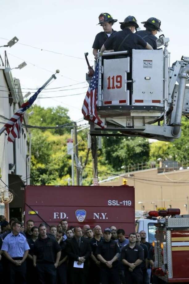 Firefighters on the ground watch as other firefighters hang bunting in honor of Lt. Gordon Ambelas in New York, Sunday, July 6, 2014. The Fire Department of New York is mourning the death of Ambelas, who became trapped while looking for victims in a public-housing high-rise blaze, the first to die in the line of duty in more than two years. Ambelas died Saturday after suffering multiple injuries while on the 19th floor of the 21-story building in the Williamsburg section of Brooklyn, officials said. Photo: Seth Wenig