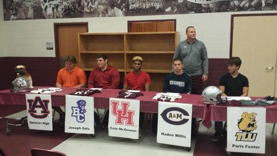 Magnolia football coach Sterling Doty speaks as (from left) Spencer Nigh (Auburn), Joseph Sols (Bethel College), Cole McGowan (Houston), Haden Willis (Texas A&M-Commerce) and Paris Foster (Texas Lutheran) prepare to make their college intentions Thursday morning at Magnolia High School.