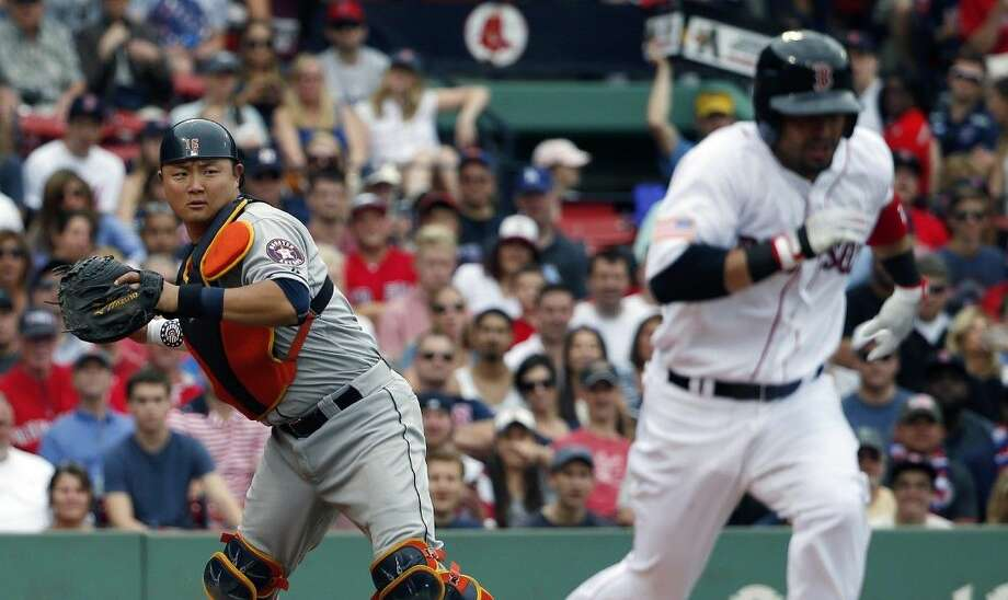 Houston Astros' Hank Conger, left, throws to first on the ground out by Boston Red Sox's Shane Victorino, right, during the fourth inning of a in Boston, Saturday. Photo: Michael Dwyer