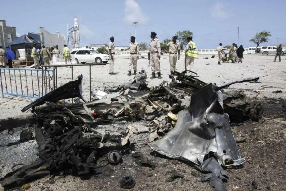 Somali soldiers stand near the wreckage of a suicide car bomb near the Somali parliament in Mogadishu, Somalia, Saturday. Photo: Farah Abdi Warsameh
