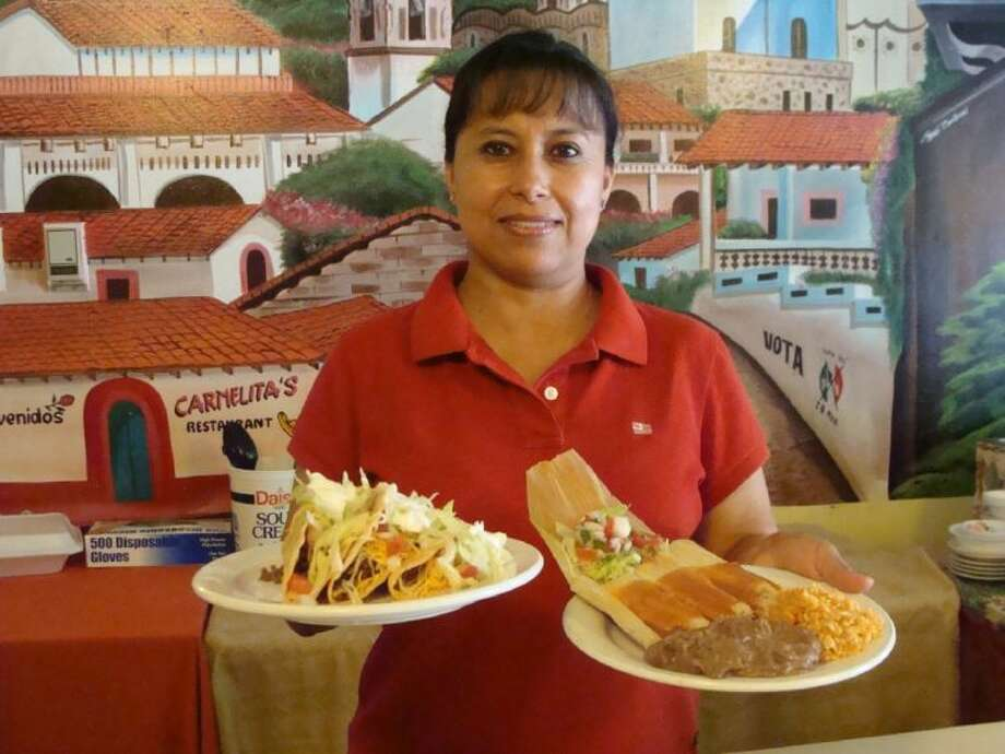 Carmelita's owner Carmen Overbay offers a plate of tacos and her famous tamales with rice and beans. Both are usually featured on the lunch buffet at Carmelita's.