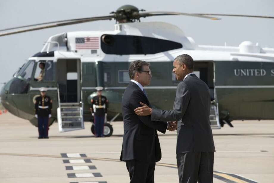 President Barack Obama is greeted by Texas Gov. Rick Perry as he arrives at Dallas/Fort Worth International Airport Wednesday.