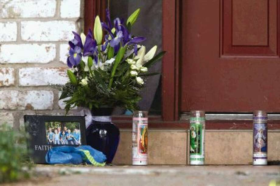 Candles, flowers and a framed family photo sits on the doorstep of a home where six people were shot Thursday in Spring. Four children and two adults were killed Wednesday after an apparent domestic dispute. / Conroe Courier / HCN