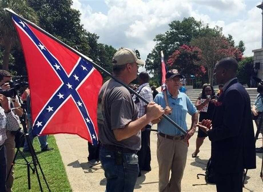 Randy Saxon, left and Wayne Whitfield, both of Anderson, S.C., discuss the Confederate flag on the South Carolina Statehouse grounds with Brodrick S. Hall of Atlanta, right, on Monday. Lively discussions on the flag took place on the grounds took place outside the state house where lawmakers debated whether the flag should be removed from the downtown Columbia complex. Photo: Meg Kinnard