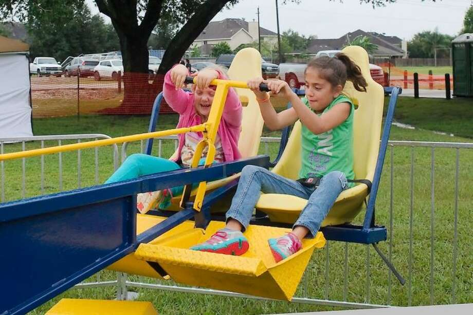 """Olivia Sutcliffe and Victoria Manrique take a spin on the """"Wizard"""" amusement ride during the Pearland International Festival Saturday, Sept. 21. Photo: KIRK SIDES"""