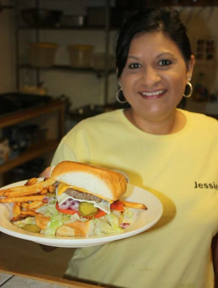 Jessie Mann grills hot, fresh burgers made to order at her restaurant, The Big Kahuna, in Cleveland. Cooking for others is something Jessie loves to do. Photo: RACHEL HALL