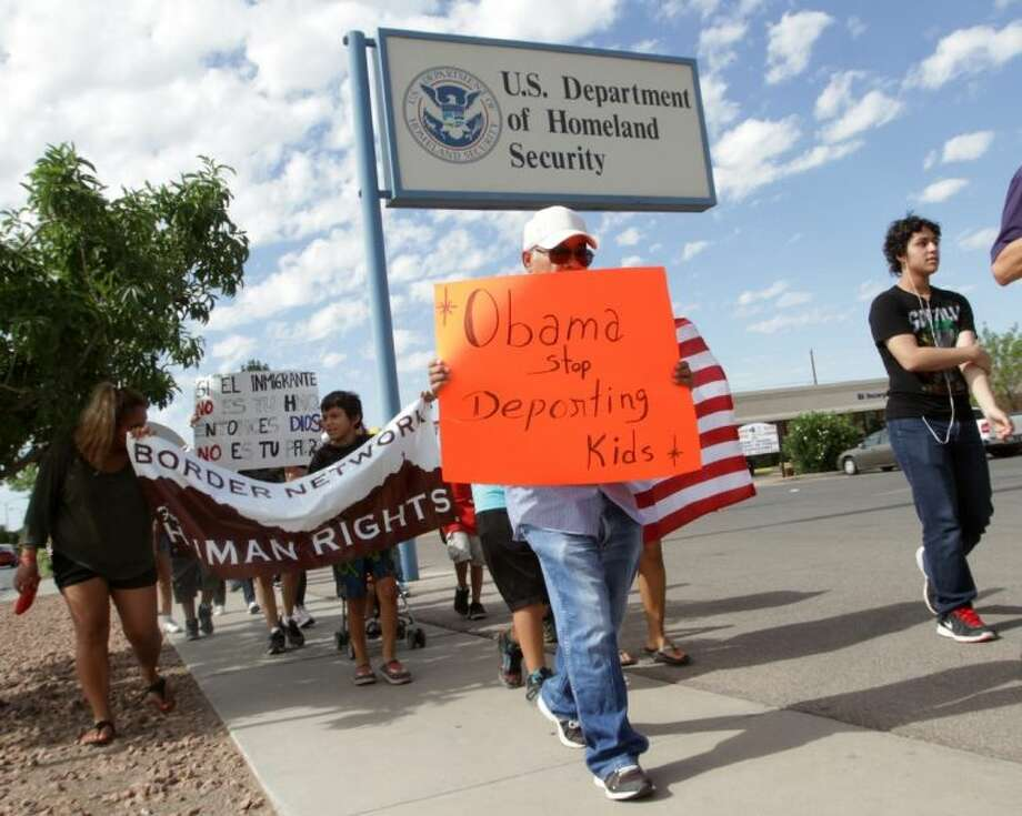 Marchers held signs as they made their way to Department of Homeland Security offices, protesting immigration policies Thursday in El Paso.