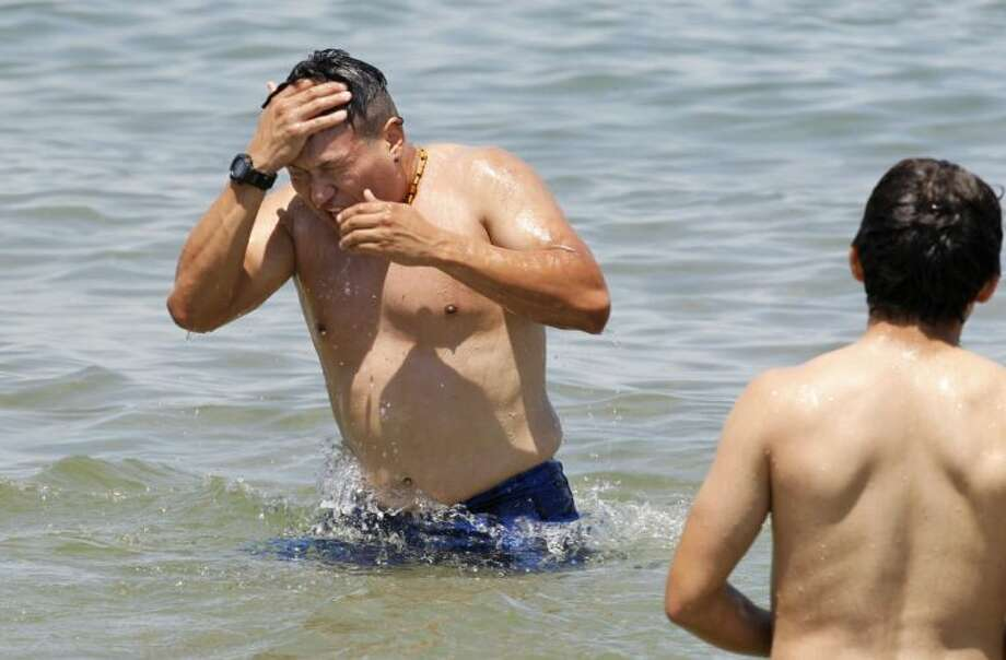 Gerald Alban, 22, reacts after diving into the cold water at the lake front Friday in Chicago. Unseasonably cool temperatures will arrive next week in the Midwest and as far south as Arkansas and Oklahoma. Chicago would normally see highs in the 80s and lows in the mid-60s, but the weather service says highs early next week will be in the mid-60s and lows could dip into the upper 40s.