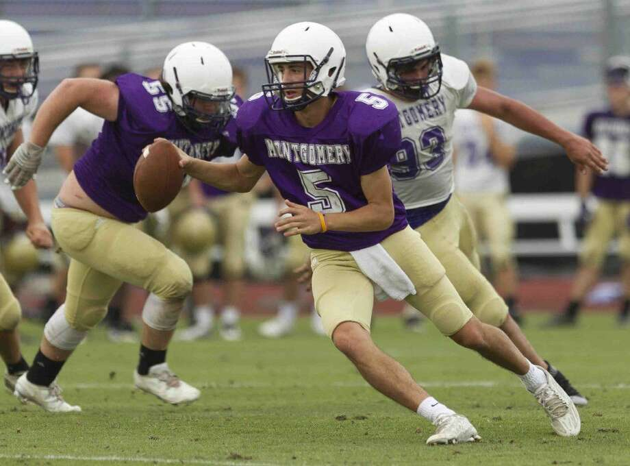 Montgomery quarterback Jordan Hood scrambles under pressure during a spring football game Wednesday in Montgomery. Go to HCNpics.com to purchase this photo and others like it. Photo: Jason Fochtman