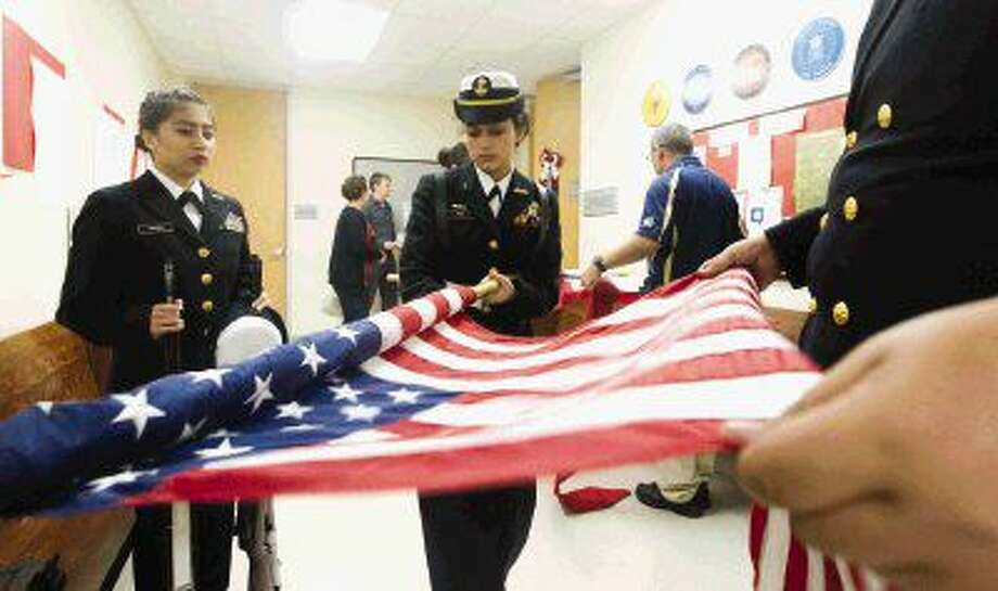 New Caney's Alberto Saldana, left, helps Ruth Rubio roll the American flag after members of the New Caney JROTC presented the colors during the veterans treatment court ceremony Wednesday in Conroe.