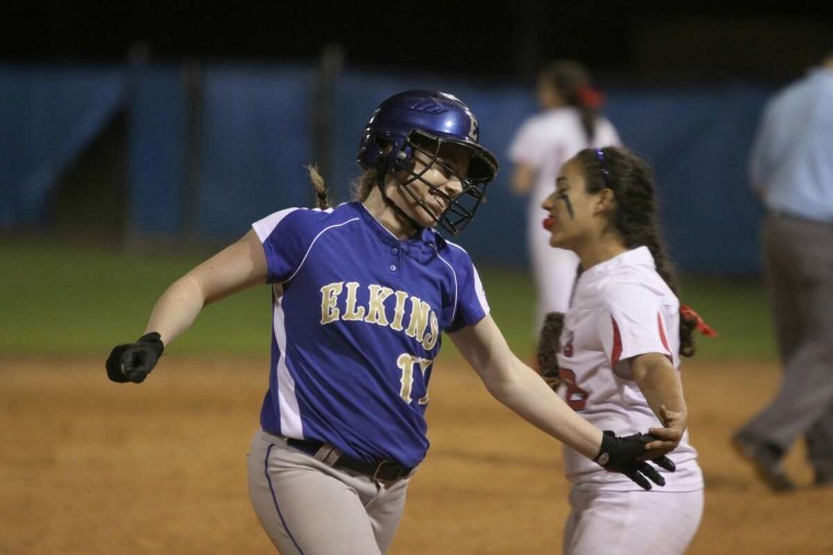 Elkins Kari Williams gets a hand slap from Dulles Megan Salazar after her home run in the first inning Tuesday night. Elkins won the game, 3-0. (Photo by Alan Warren)