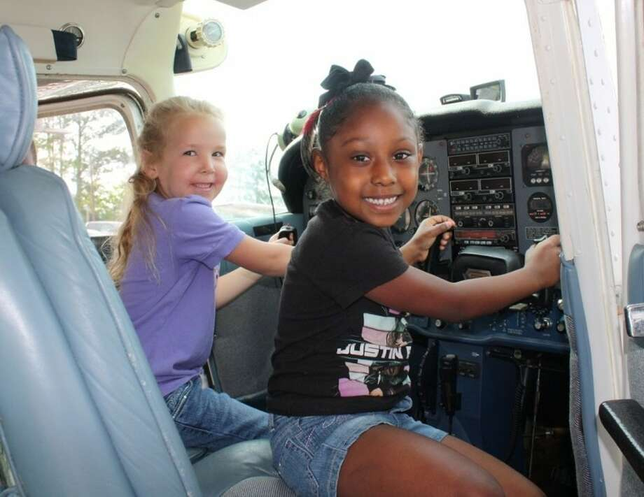 Heather Perry and Monica Bryans act as pilot and co-pilot of a small plane at the Cleveland Municipal Airport. Photo: Stacey Gatlin