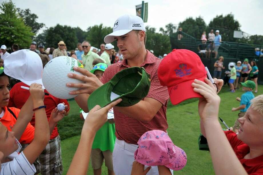 PGA golfer Jordan Spieth signs autographs at the John Deere Classic as he arrives to the practice range, Tuesday in Silvis, Ill. Photo: Paul Colletti