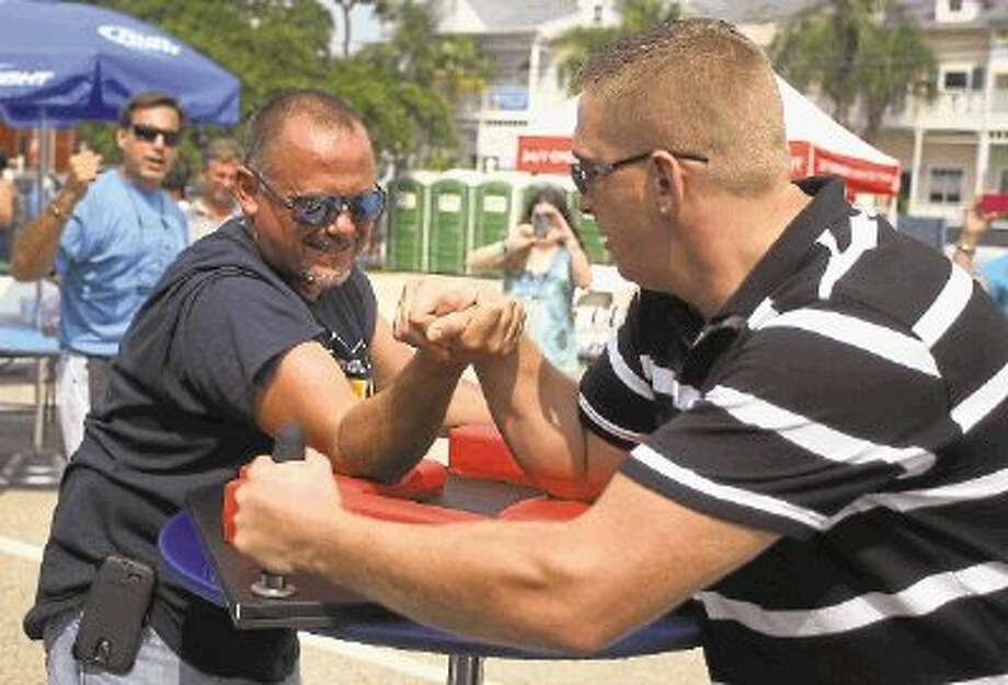 Ray, left who works for the City of Seabrook takes on Marios from Greece at the Spartan Arm Wresting during the Kemah Greek Food and Wine Fest Saturday 14th. Photo: Kar B Hlava / @WireImgId=2642722