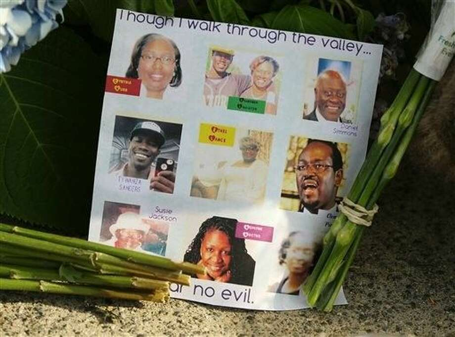 A note on the sidewalk includes photos of the nine who were killed at a memorial in front of the Emanuel AME Church on Friday, June 19 in Charleston, S.C. Dylann Storm Roof, 21, is accused of killing nine people during a Wednesday night Bible study at the church. Photo: Curtis Compton