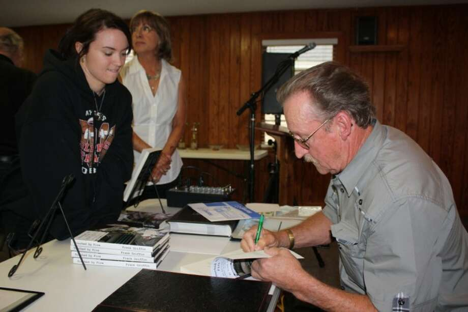 """Frank Griffin, right, signs a copy of his book, """"Touched by Fire,"""" for Karly Yaws, left. Photo: MELECIO FRANCO"""