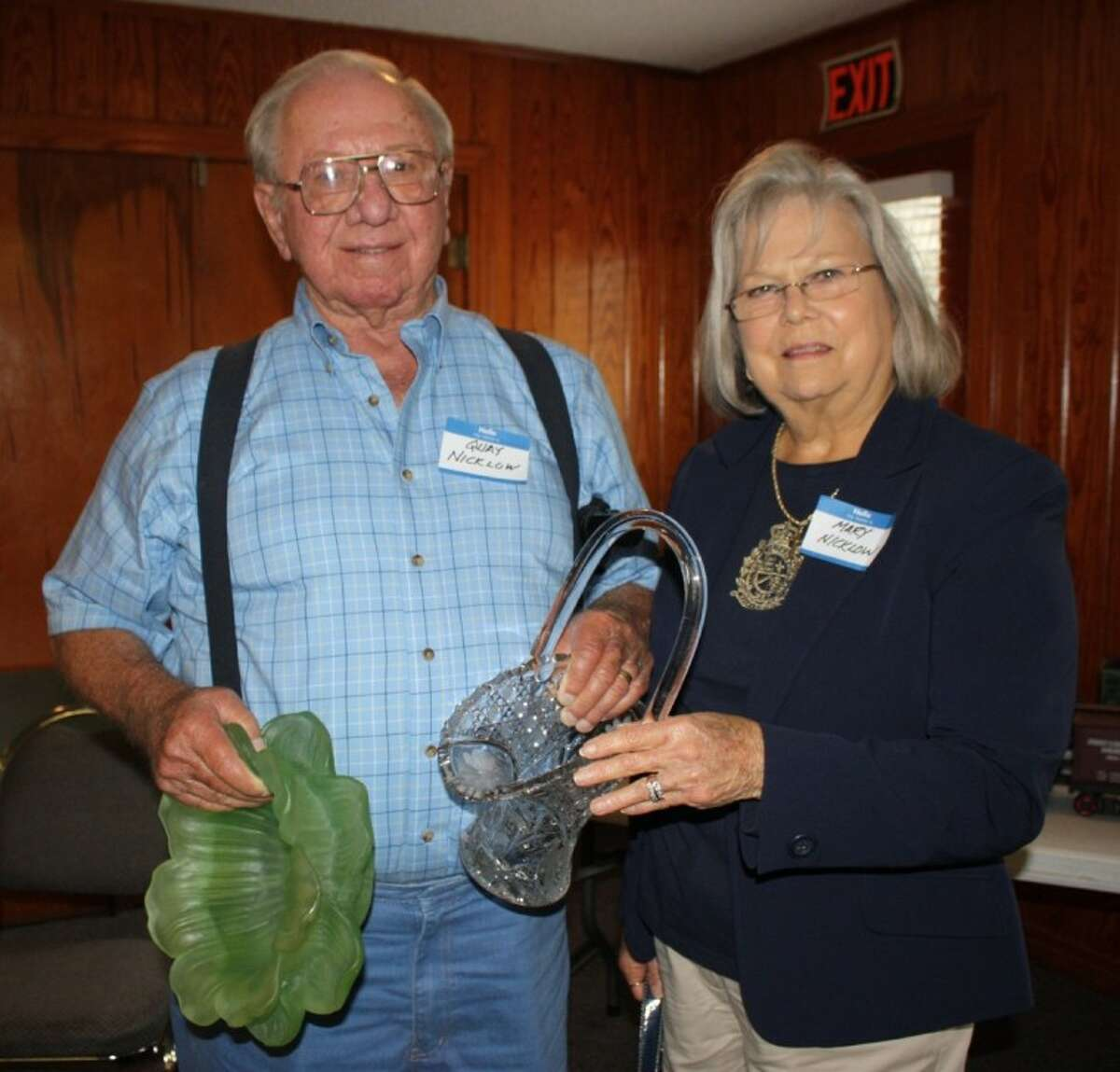 Quay Nicklow, left, and Mary Nicklow, right, display some of the silent auction items they won at the Coldspring Public Library's annual book review and dessert party.