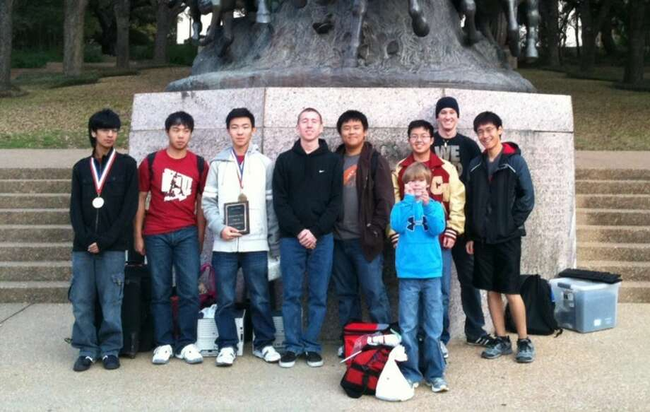 Cypress Woods computer science students (from left) Nikoli Cartagena, Henry Chen, Andrew Liu, Jason Krezinski, Ben Lin and Thomas Lam and former Cypress Woods students Harry Dibenedetto and Darius Xu-now in the Turing Honors Computer Science program at UT Austin-celebrate Cypress Woods' strong showing at the UT Computer Science Contest this weekend. Pictured, in front, with the students is the son of Cypress Woods computer science teacher Stacey Armstrong, Ben Armstrong. Photo: From CFISD