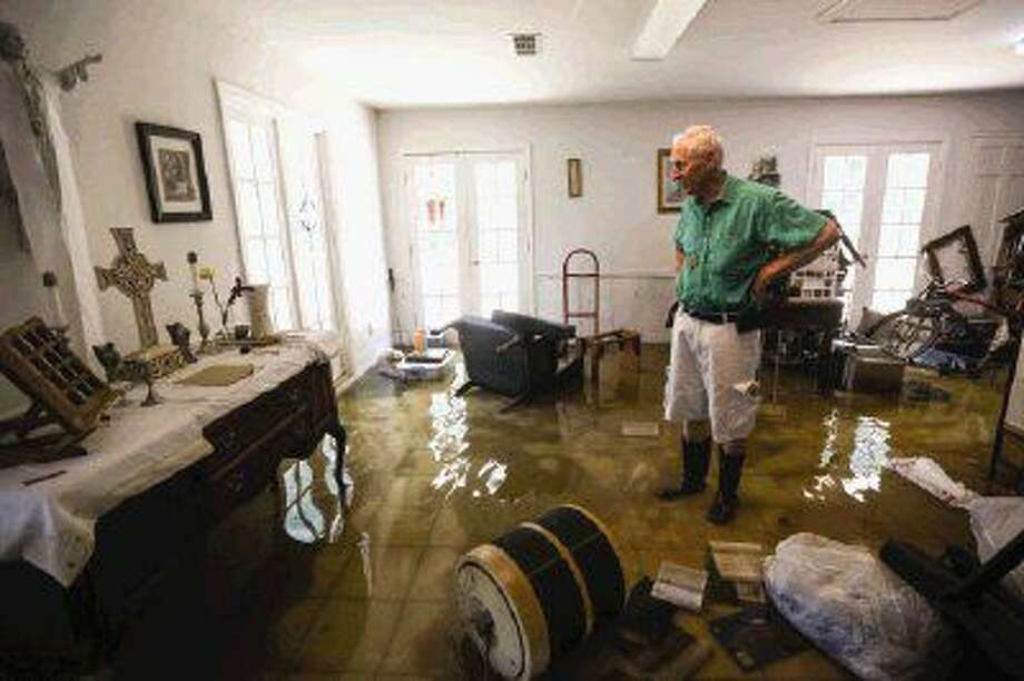 River Plantation resident Kenneth Walsh on Sunday surveys damage to the home he and his wife Eileen share.