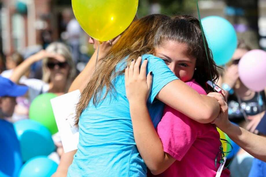 Mourning attendees hug during a memorial service for the Stay family at Lemm Elementary School on Saturday in Spring. Cassidy Stay, 15, spoke at Saturday's memorial. She was grazed in the head during Wednesday's attack that killed her parents and four siblings. She played dead until the shooter left, then despite suffering a fractured skull managed to call 911.
