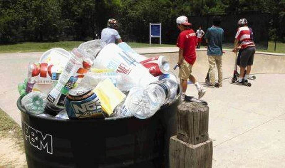 Trash overflows in a bin at Bear Branch Skate Park as children wait their turn. Members of The Woodlands Township staff are working with teens to keep the park clean for all users.