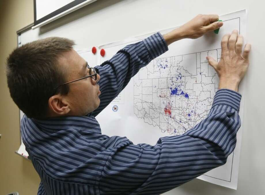 In this June 26 file photo, Austin Holland, research seismologist at the Oklahoma Geological Survey, hangs up a chart depicting earthquake activity at their offices at the University of Oklahoma in Norman, Okla. Photo: Sue Ogrocki