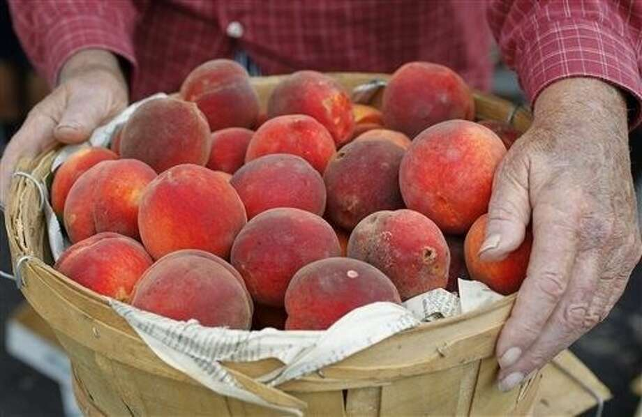 John Doak, a longtime Montague County peach grower, sells his produce at Cowtown Farmers Market in Fort Worth Wednesday. Some Texas growers, including Doak, are expecting a plentiful peach harvest in spite of heavy spring rain and flooding that left some fields impassable. Photo: David Kent
