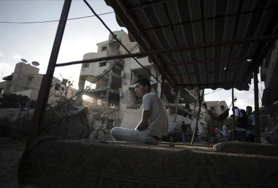 A Palestinian man sits on a cart next to the house of Hamas leader, Mahmoud Zahar, that was damaged in an early morning Israeli missile strike in Gaza City, Wednesday, July 16, 2014. Israel on Wednesday intensified air attacks on Hamas targets in the Gaza Strip following a failed Egyptian cease-fire effort, targeting the homes of four senior leaders of the Islamic militant movement and ordering tens of thousands of residents to evacuate border areas. Photo: Khalil Hamra