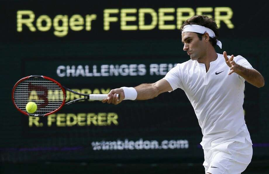 Roger Federer of Switzerland returns a shot to Andy Murray of Britain, during their men's singles semifinal match at the All England Lawn Tennis Championships in Wimbledon, London, Friday. Photo: Kirsty Wigglesworth
