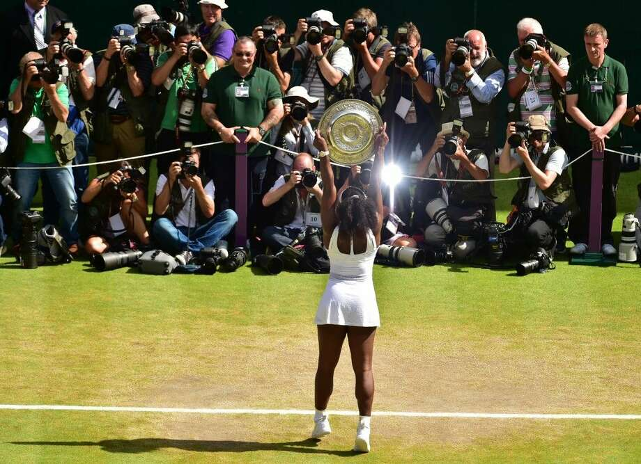 Serena Williams of the United States holds up the trophy toward the media after winning the women's singles final against Garbine Muguruza of Spain at the All England Lawn Tennis Championships in Wimbledon, London, Saturday. Photo: Dominic Lipinski