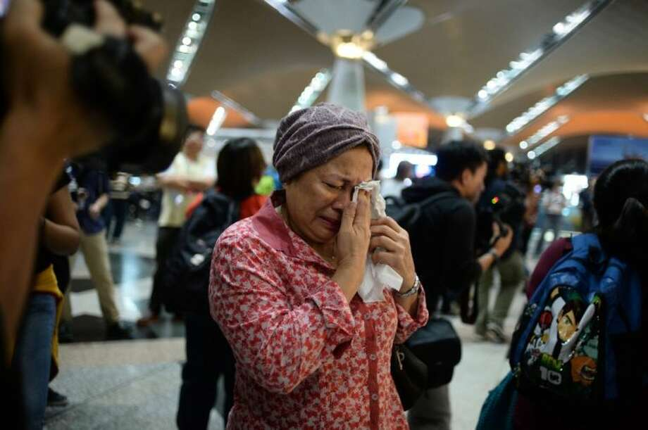 ABOVE: A woman reacts to news regarding a Malaysia Airlines plane that crashed in eastern Ukraine at Kuala Lumpur International Airport in Sepang, Malaysia, Friday, July 18, 2014. Ukraine said a passenger plane carrying 295 people was shot down Thursday as it flew over the country, and both the government and the pro-Russia separatists fighting in the region denied any responsibility for downing the plane. Photo: Joshua Paul