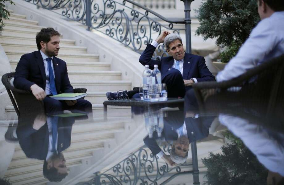 U.S. Secretary of State John Kerry, centre, and State Department Chief of Staff Jon Finer, left, meet with members of the U.S. delegation at the garden of the Palais Coburg hotel where the Iran nuclear talks meetings are being held in Vienna, Austria, Friday. Photo: CARLOS BARRIA